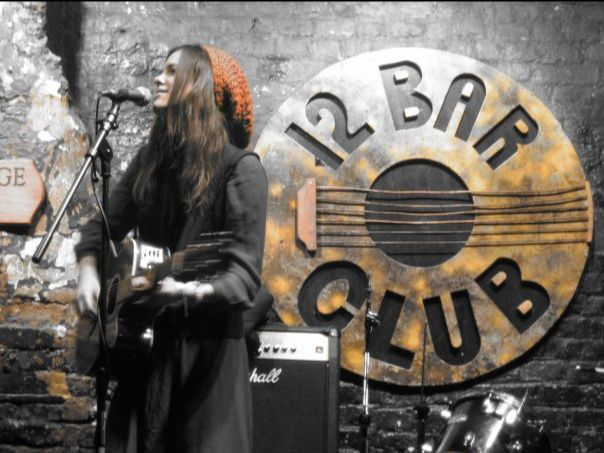 Rags Nordset wears and orange hat and sings into a microphone while playing her guitar in front of a sign reading '12 Bar Club'
