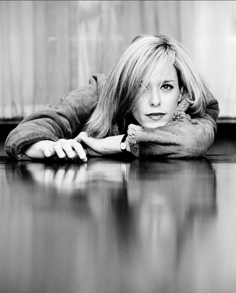 Black and White image of Ragz Nordsert resting her head and arms on a table. The surface is reflective and her hair covers one eye.